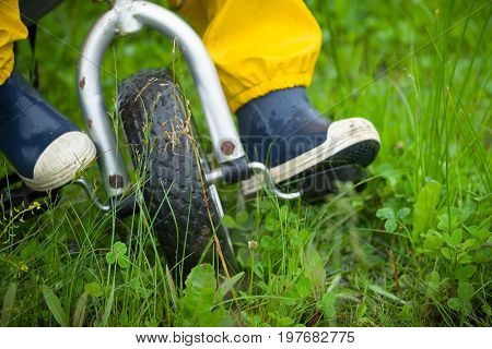 Closeup of toddler child feet in rubber boots and pants riding a bicycle on green grass. Boy walking outdoors after the rain.