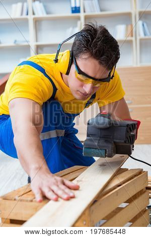 Repairman carpenter polishing a wooden board with an electric