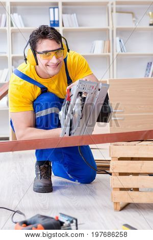 Repairman carpenter cutting sawing a wooden plank with a circula