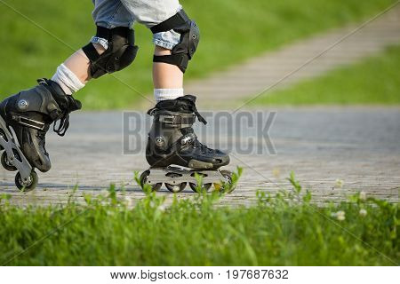 Closeup view of black roller skates or rollerblading. Roller skate legs of a child in the park. Boy's legs in roller blades.