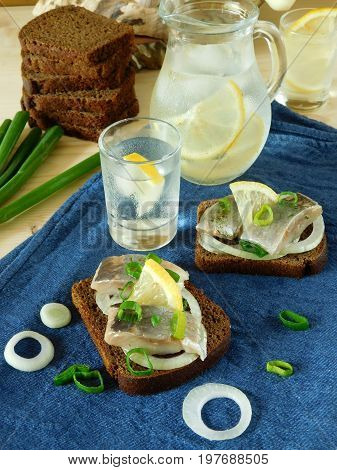 Salted herring with onion and lemon on a slice of bread and misted glass vessels filled with drink in the background
