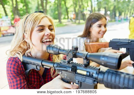 Portrait of two beautiful women aiming with big rifle at outdoor game tent in amusement park
