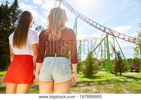 Back view portrait of two young women holding hands standing against huge roller coaster ride