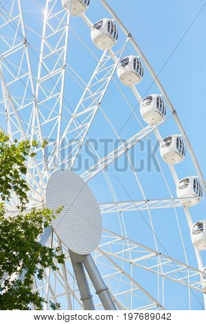 Angle view of tall modern Ferris wheel against blue sky in amusement park