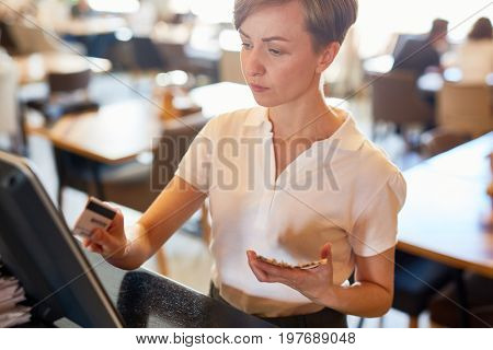 Clerk of coffee-shop carrying out payment procedure through computer