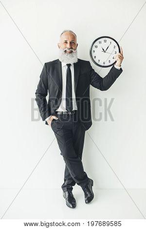 Smiling Mature Businessman Holding Clock On Ligth Background