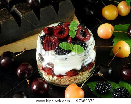 Oatmeal with yogurt and berries in a jar surrounded by two sorts of cherries and blackberries. Layered breakfast