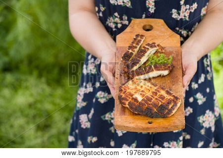 Top view on two grilled slices of homemade halloumi cheese on wooden borad in woman's hands. Outdoors. Grilling season. Healthy eating.