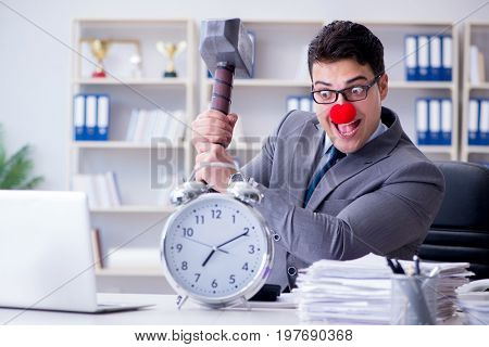 Clown businessman in the office with hammer and an alarm clock