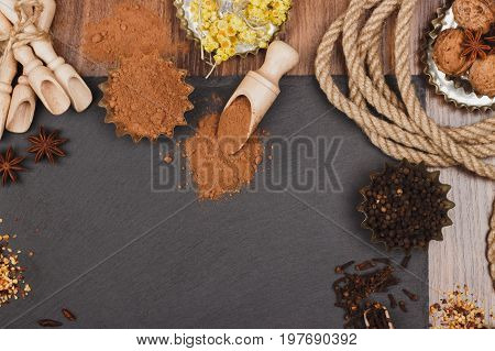 Different Spices In Bakeware With Wooden Scoops On The Slate Slone Background