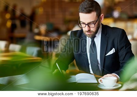 Elegant trader sitting in cafe and making notes in notebook