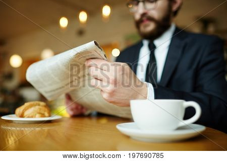 Newspaper in hands of jobless man having coffee in cafe