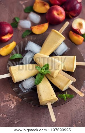 Peach popsicle on concrete background, popsicle top view.