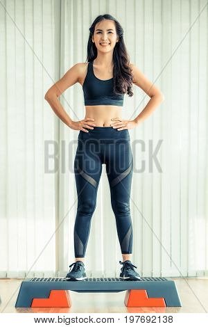 Sporty Woman Standing On Aerobic Stepper In Gym