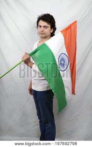 young indian male model in white tshirt holding indian flag
