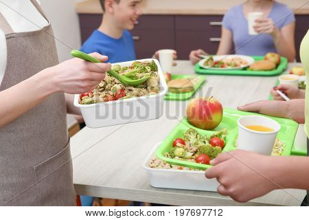 Young woman serving lunch to children at school canteen