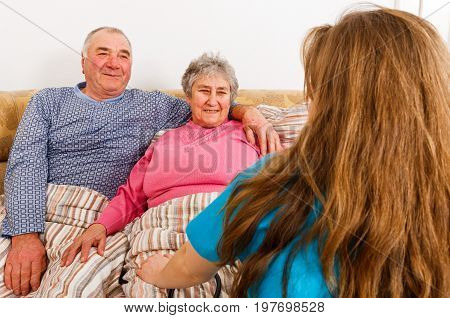 Photo of elderly couple and young female doctor