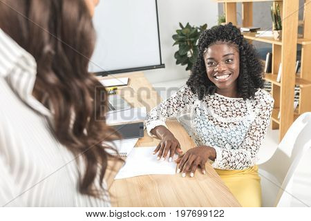 Portrait Of Smiling African American Woman Talking With Colleague Wile Sitting At Workplace In Offic