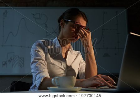 Tired businesswoman sitting in front of laptop in office late in the night