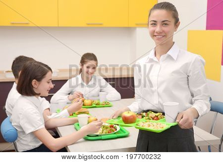 Cute girl holding tray with delicious food in school canteen