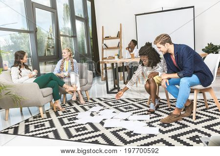Multicultural Business People Looking At Papers On Floor Together In Office