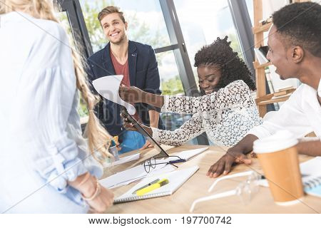 multicultural smiling business people discussing work at meeting in office