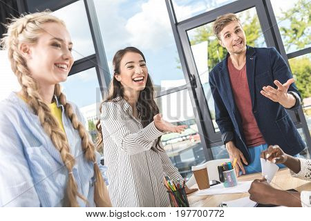 Multicultural Young Business People Having Conversation At Workplace In Office