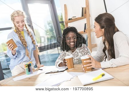 Portrait Of Multicultural Young Businesswomen With Coffee To Go At Workplace