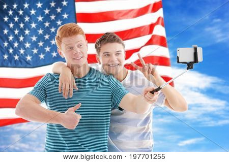 Friends tacking selfie and USA flag on background