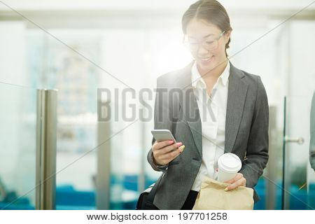 Portrait of beautiful Asian businesswoman looking at smartphone screen and smiling while leaving office for coffee break
