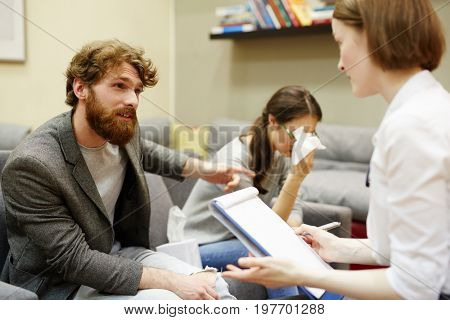 Portrait of young family quarreling and arguing in doctors office at couples counselling sessionAngry Man Complaining about Wife to Psychiatrist