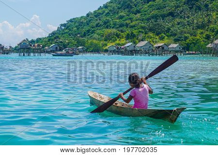 Semporna,Sabah,Malaysia-Apr 23,2017:Sea Gypsy kid girl rowing an unique handmade boat surrounded by beautiful clear water of the Bodgaya island,Semporna,Sabah,Malaysia.