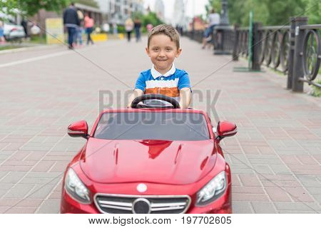 Smiling little boy driving by toy car. Active leisure and sports for kids. Portrait of happy little kid on the street. Funny cute children making vacations and enjoying summer. Healthy lifestyle.