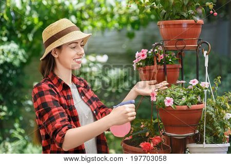 portrait of happy young woman gardener spraying water on flowers. Girl with sprayer bottle spraying pesticide. People, gardening, care of plants, hobby concept