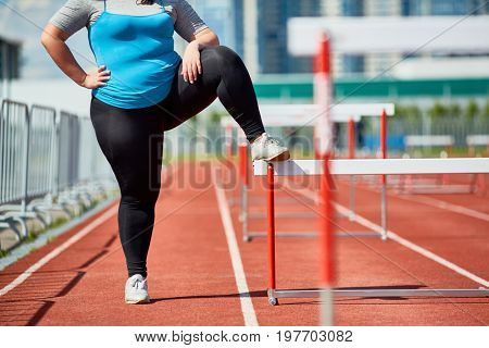 Confident and ambitious chubby female in activewear standing on racetrack and keeping one leg on hurdle