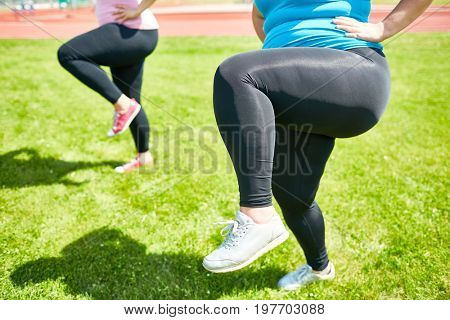 Fat woman bending her knee while raising leg during training on green lawn