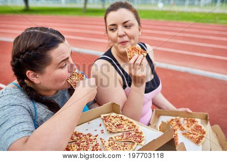 Happy young over-size women eating tasty and appetizing pizza after workout on stadium