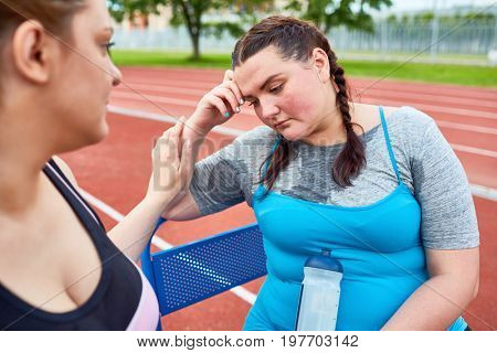 Sad woman with bottle of water sitting on bench after tiresome workout while friend encouraging her not to quit training