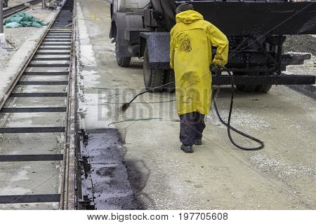 Worker Sprays Bitumen Emulsion Onto The Road