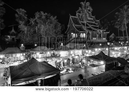 LUANG PRABANG LAOS - MARCH 11 2017: From the top black and white picture of Haw Pha Bang and Night Market located on the grounds of the Royal Palace Museum in Luang Prabang Laos.