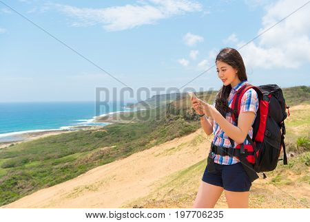 Happy Female Hiker Using The Mobile Smart Phone