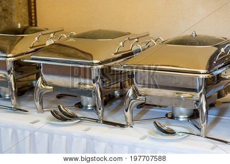 banquet table with chafing dish heaters. White Plates