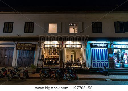LUANG PRABANG LAOS - MARCH 11 2017: Night shoot of coffee shops and stores at Sisavangvong Road located in the olf Quarter of Luang Prabang Laos.