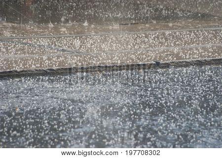 Rain and Hailstones falling on urban asphalt and tramline.