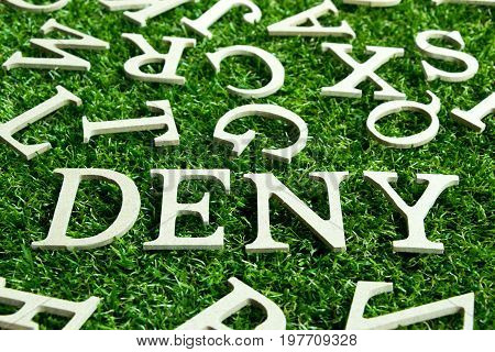 Wording deny on artificial green grass with another english alphabet background