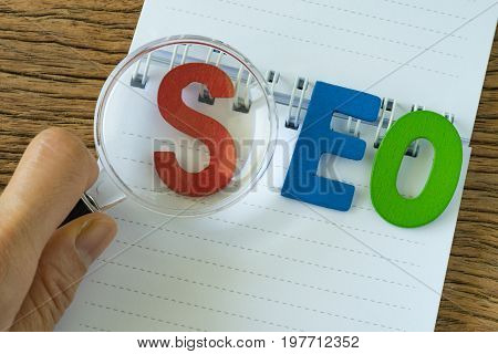 hand holding magnifying glass on colorful alphabets abbreviation SEO on white note paper on the wooden table as SEO Search engine optimisation concept.