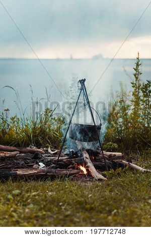 Travel a kettle over a fire burning on the river and sunset backgroun. Cooking over a campfire.