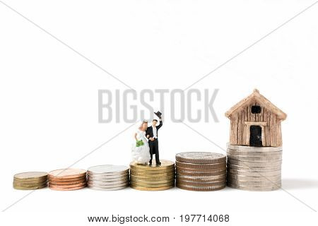 Miniature people wedding  on stack coins  on white background.