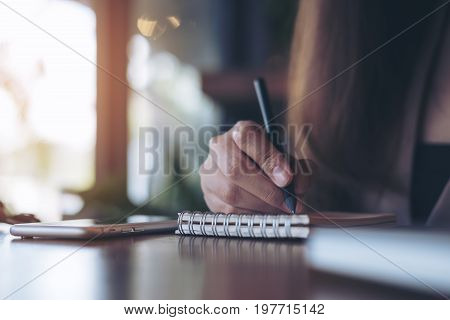 Closeup image of a woman holding pencil and writing on notebook with white mobile phone on wooden table in cafe