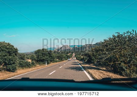 Road With Mountain Landscape Seen Through Windshield Of Car. Sardinia. Italy.